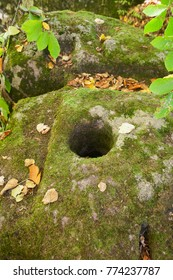 Hole in dolmen ruins covered by moss in a forest
