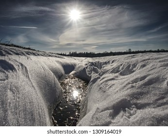 Hole in icy snow with sun flares. Lovely winter scene.