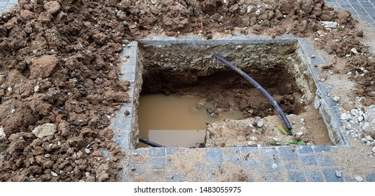 Hole for installation pillar or pole on cement ground with water and black wire cable at construction site and no strict and make symbol to tell danger area- Unsafe, Safety and structure
