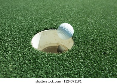 Hole in one.  A successful putt.  Golf ball falling into hole.