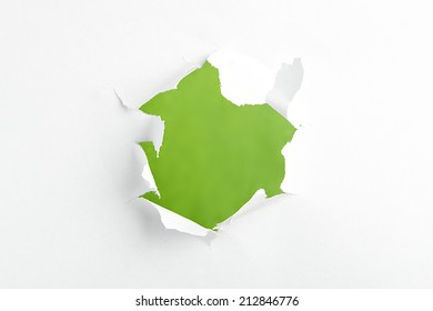 Hole in paper on green background inside