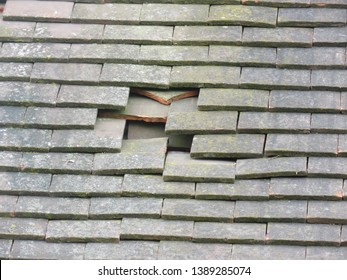 Hole in a pitched roof, broken clay tiles