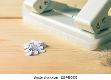 hole puncher with paper confetti on wooden table