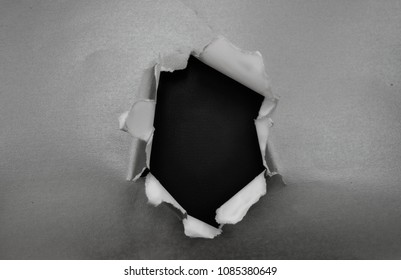 A hole ripped in silver material with dark center