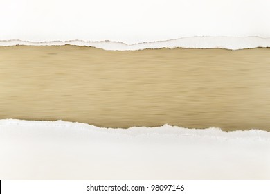 Hole ripped in white paper on brown background. Copy space