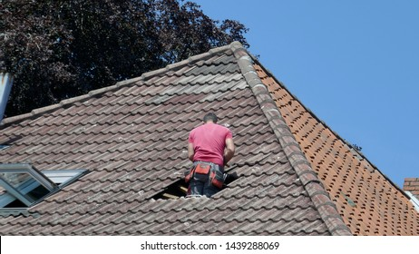 Hole in the roof of a residential building. Repair of a tile roof after a storm damage.