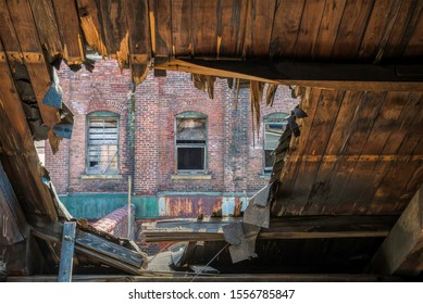 A hole in the roof shows another wing of the old Scranton Lace Factory across the courtyard.  Image taken at the old Scranton Lace Factory, built in 1890, closed in 2002, demolished in 2019.
