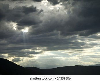 A hole in a stormy cloud let a ray of light pass trough.