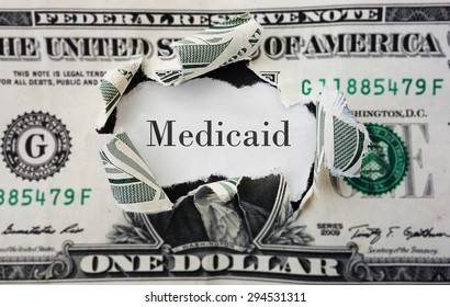 Hole torn in a dollar bill with medicaid text
