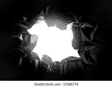 hole torn in a piece of metal, with light shining thru