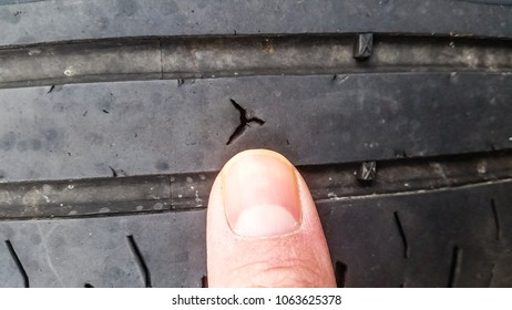 Hole in tyre of motor vehicle at close-up, size meassured with thumb of human person