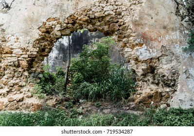 Hole in the wall of abandoned stone building.