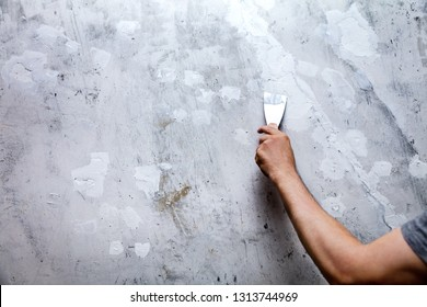 Holes and cracks in a wall are filled with filler or gypsum