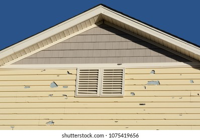 Holes in exterior siding in home from damage by hail storm