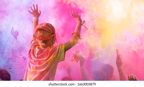 Holi Fest: Enthusiastic people cheer happy at a Holifestival, dancing and throwing with colorful Holi powder