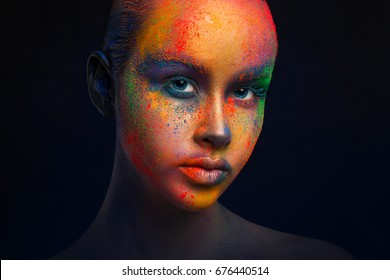 Holi festival of colors background. Female face art with creative make up. Closeup cropped studio portrait of young fashion model on black with copy space