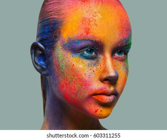 Holi festival of colors. Female face art with creative make up. Closeup studio portrait of young fashion model isolated on gray background with bright colorful mix of paint