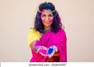 Holi Festival Of Colours. Portrait of happy indian girl in traditional hindu sari on holi color . india woman silver jewelry with powder paint on dress ,colorful pink and blue hair in Goa Kerala