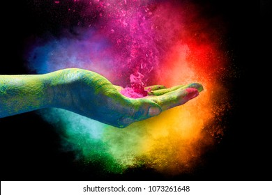 Holi festival concept. Magical rainbow colored powder exploding from the palm of a cupped hand creating a vibrant cloud of dust in the colors of the spectrum over a black background.