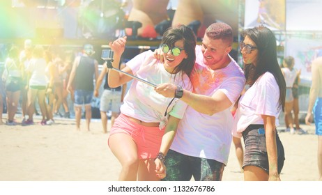 holi party on beach young friends having fun taking selfie, at holi festival of colors covered with gulaal color powder background with unrecognized people. summer festival, freedom friends  concept.