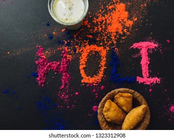 'HOLI' word written by power color along with holi special sweet- Gujia and Bhaang milk. Indian festival Holi Greetings background photo.