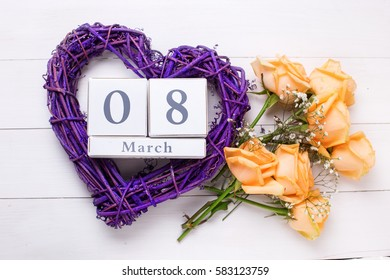 Holiday 8 March background. Big violet heart, peach color roses flowers and  calendar on white wooden planks.  Selective focus.