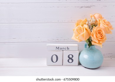 Holiday 8 March background with flowers. Peach color roses flowers, burning candles  and  calendar on white wooden planks.  Selective focus is on calendar.