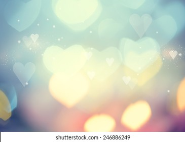 Holiday abstract glowing blurred background, bokeh. Defocused blinking heart shaped lights, vintage toned. Valentine Hearts Abstract Background. St.Valentine's Day Wallpaper. Heart Holiday Backdrop