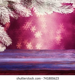 Holiday background with Christmas tree branches over snowflake-shaped lights