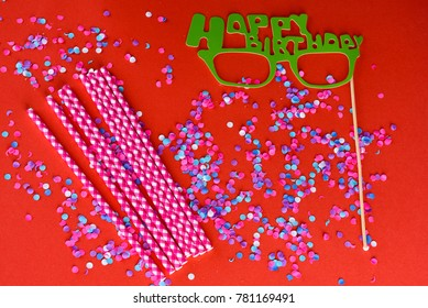 Holiday background with colorful confetti, carnival mask paper glasses Happy birhday and striped Drinking straws. Flat lay style. Birthday or party greeting card with copy space.