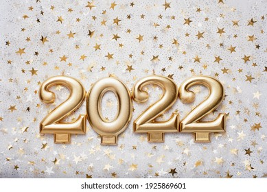 Holiday background Happy New Year 2021. Numbers of year 2022 made by gold candles on bokeh festive sparkling background. celebrating New Year holiday, close-up. Space for text
