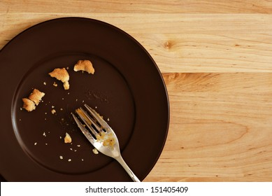 Holiday background image of all that remains of a delicious piece of pumpkin pie.  Plate with crumbs and used fork on wood background with copy space.