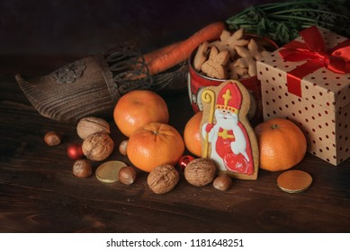 Holiday background Saint Nicholas, Sinterklaas, with traditional dutch shoe with carrots, cookies, nut, tangerines, gifts and sweets