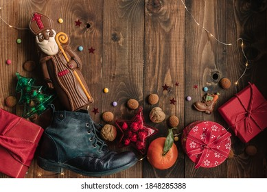 Holiday background Saint Nicholas, Sinterklaas, with child's shoe, chocolate, cookies, nut, tangerines, gifts and sweets