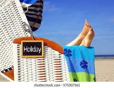 Holiday at the Beach - feet of woman in beach chair at the ocean - Summer Season