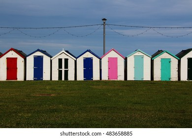 Holiday beach huts with blue sky,  grass, and telephone pole
