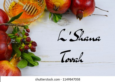 Holiday border on white washed rustic wooden table for Jewish holidays of Rosh Hashana or Yom Kipper. Includes apple, pomegranate and honey with honey dipper. Holiday greeting added.