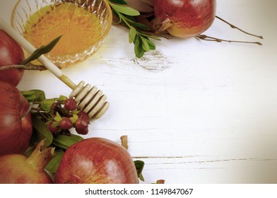Holiday border on white washed rustic wooden table for Jewish holidays of Rosh Hashana or Yom Kipper. Includes apple, pomegranate and honey with honey dipper. Copy space