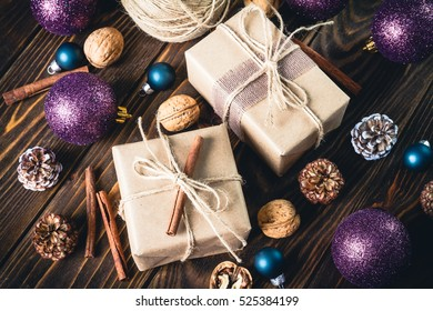 Holiday Boxes with Gifts and natural twine, balls, pine cones, walnuts, cinnamon, fir tree toys on wooden background. Toned. Vintage Style