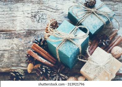 Holiday Boxes with Linen Cord, Cinnamon, Pine cones, Nuts. Natural Gifts on Wooden Background. Toned