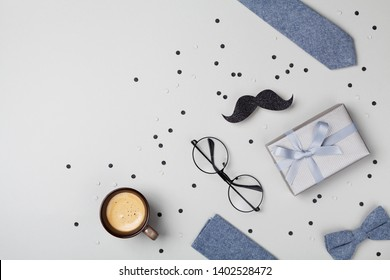 Holiday breakfast on Happy Fathers Day with cup of coffee, gift box, glasses, bowtie and moustache top view. Flat lay.