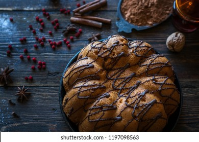 Holiday cake on wooden table with berry, spice and chocolate at rustic home kitchen. Christmas baking background. Ingredients for cooking on dark wooden background. Homemade festive food. Toned image