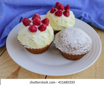 Holiday cakes (muffins) with raspberries on wooden background.