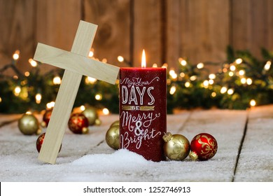 Holiday candle with wood cross and Christmas garland with lights and red and gold ornaments border; festive religious background