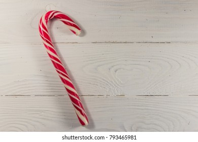 Holiday candy cane on white wooden table