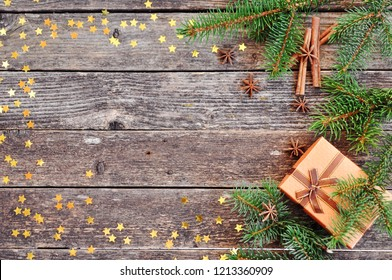 Holiday card for the new year is 2019 in warm, trendy colors. Christmas composition of spruce branches, gift, cinnamon, anise and confetti stars on rustic wooden background. Flat plan, top view