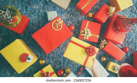 Holiday or celebrate Concept. Beautiful female hands holding Christmas present wrapped in kraft paper with set of colorful Christmas gifts lying on a retro navy blue carpet background. Vintage style.