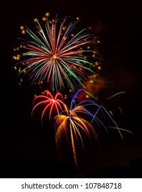 Holiday Celebration Fireworks Display - Exploding fireworks light up the night sky in a beautiful pyrotechnic display.