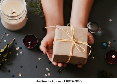 holiday celebration and gratitude expression. hands giving present wrapped in craft paper. assortment of seasonal adornments on blue background.