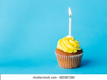 holiday, celebration, greeting and party concept - birthday cupcake with one burning candle over blue background